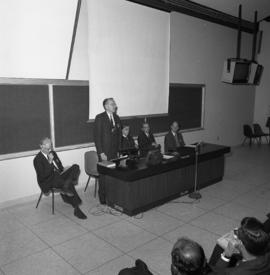Photograph of an unidentified person speaking at the front of a classroom
