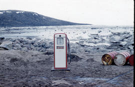 Photograph of an Esso gas pump and three barrels