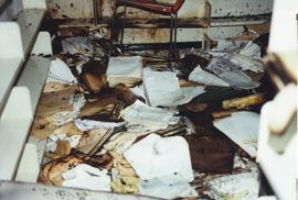 Photograph of fire damaged documents piled on the floor