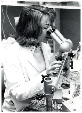 Photograph of individual looking through microscope
