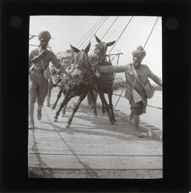 Photograph of unidentified soldiers crossing bridge with cart and donkeys