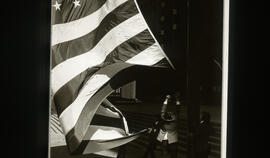 Photograph of people next to a large American flag