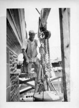 Photograph of a man lifting something with chains and pulleys