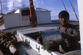 Photograph of a man emptying a bucket on a small boat