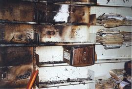 Photograph of fire damaged shelves and documents