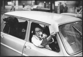 Photograph of an unidentified pro-war demonstrator gesturing out of the passenger seat of a car d...