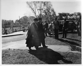 Photograph of two unidentified people in robes walking outside