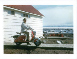 Photograph of Barbara Hinds sitting on a red scooter in Frobisher Bay, Northwest Territories