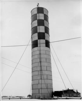 Photograph of an unidentified radio tower, checkered at top