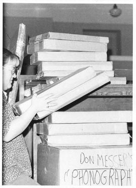 Photograph of Mary Ellen Wright packing the Don Messer collection