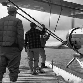 Photograph of three men from St. Felicien Air Serivces next to a sea plane in northern Quebec