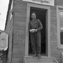Photograph of an unidentified man standing in a doorway in Dawson City, Yukon