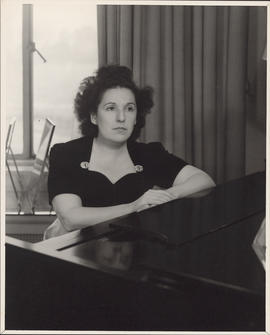 Publicity photograph of Ellen Ballon sitting at a piano