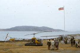 Photograph of several people standing by a helicopter in Cape Dorset, Northwest Territories