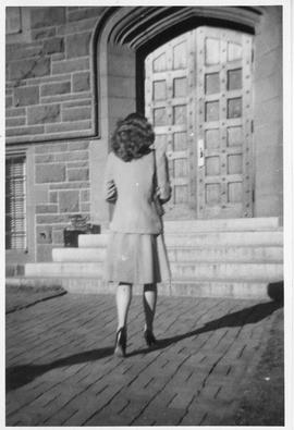 Photograph of an unidentified person walking toward a door