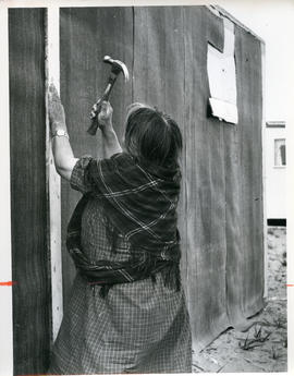 Photograph of Alicie Berthé hammering a nail into her house