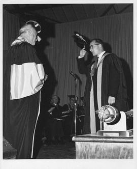 Photograph of Henry Hicks greeting an unidentified person at a convocation ceremony