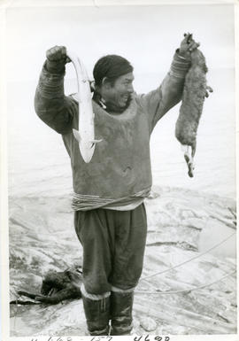Photograph of Stan Annanak holding a fish and a rabbit near Ungava Bay