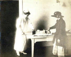 Photograph of Health Centre No. 1 nurse measuring baby