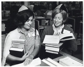 Photograph of two women looking at books
