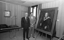 Photograph of Chester Stewart with a painting of himself