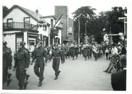 Photograph of a parade of Canadian Armed Forces and a military band marching down a street in Hol...