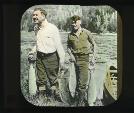 Photograph of two unidentified men carrying fish from a canoe