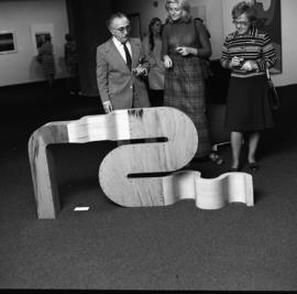 Photograph of three unidentified people with a sculpture
