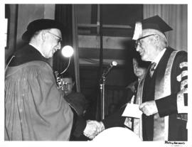 Photograph of two men shaking hands at the opening ceremony of the Sir James Dunn Building