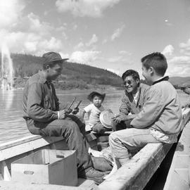 Photograph of Arthur Percy, a man, and two boys on a boat on the Yukon River