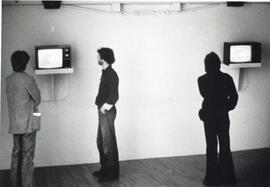 Photograph of three people watching televisions in the gallery at the Centre for Art Tapes