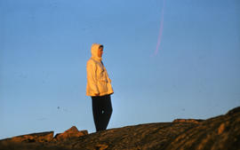 Photograph of Barbara Hinds standing on a hill near Frobisher Bay, Northwest Territories