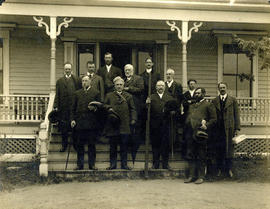 Photograph of 12 unknown individuals on the steps of a house