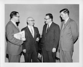 Photograph of four unidentified people talking