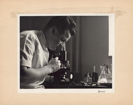 Photograph of doctor looking into microscope at the Outpatient and Public Health Clinic