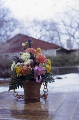 Photograph of multicolored flowers in a wicker pot