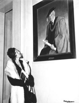 Photograph of Lady Dunn looking at a portrait of Sir James Dunn