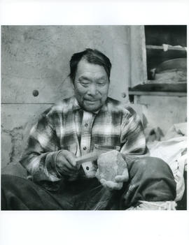 Photograph of an unidentified man working with a tool and a rock