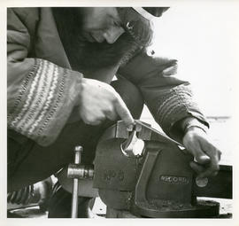Photograph of a man working with a vice in Fort Chimo, Quebec