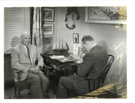 Photograph of Thomas Head Raddall and Ken Homer resting in the former's den between filming shots