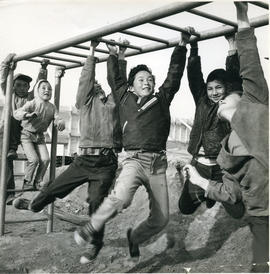 Photograph of six children playing on monkey bars in Fort Chimo, Quebec