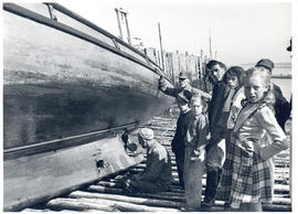 Photograph of a man looking at a hole in the keel of a salvaged boat, sitting on a beach at Seal ...