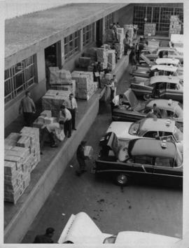 Photograph of people loading telephone directories into the trunks of Halifax taxi cabs