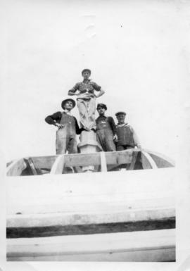 Photograph of four men standing on top of the Arts & Administration Building