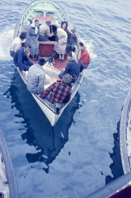Photograph of several people traveling with a new baby in a small boat in Hopedale, Newfoundland ...
