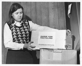 Photograph of Anna Oxley holding a box of paper for recylcling