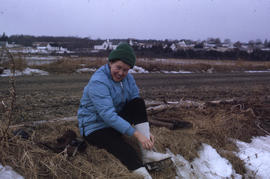Photograph of Barbara Hinds sitting on the ground and lacing ice skates