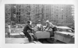 Photograph of men lifting a stone block