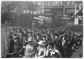 Photograph of a group of people in academic dress sitting in chairs on the Grand Parade