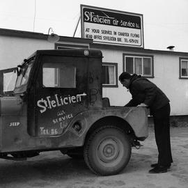 Photograph of a man looking in the back of a Jeep belonging to the St. Felicien Air Service in no...